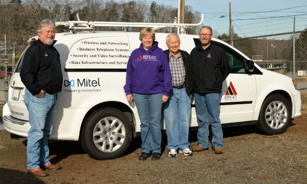 Four people standing in front of a white service van